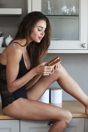 Babe in lingerie eating sandwich in kitchen Stock Photo