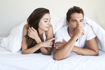 Guy ignoring brunette in bed, looking away Stock Photo