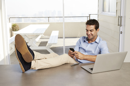 Relaxed fellow texting from office at home