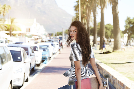 incidental people: Beautiful woman looking at camera with skateboard