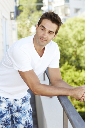 Guy leaning on balcony and looking away, content Stock Photo