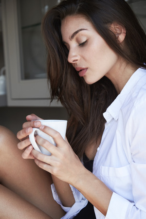 Brunette thinking over coffee, content