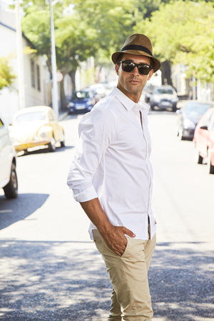 Casually clothed guy in white shirt and hat, portrait