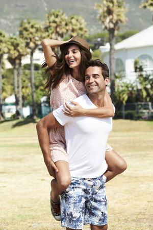 Loving couple piggyback in park