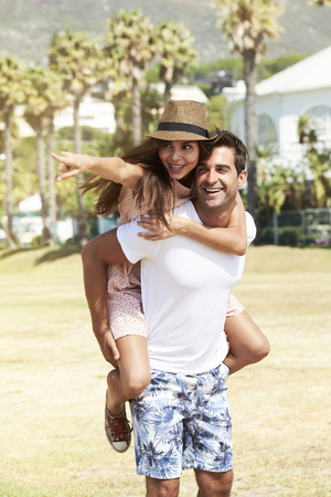Girl directs guy carrying her, smiling Stock Photo