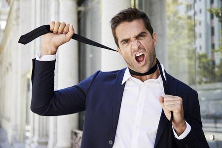 Businessman with tie wrapped around neck, portrait Stock Photo