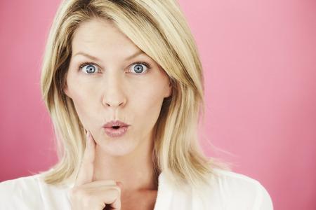 Blonde blue eyed woman looking surprised in studio