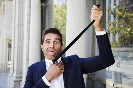 strangled: Businessman strangled by his tie, portrait