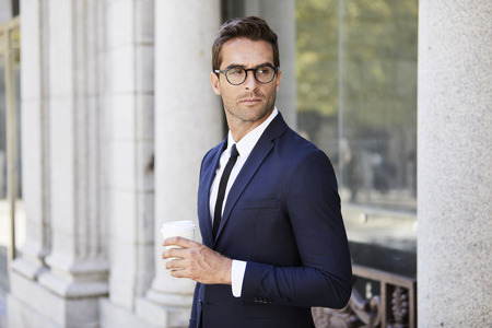 Seriously handsome businessman holding coffee and wearing glasses