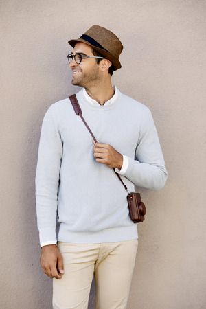 Happy guy in hat and glasses with camera case
