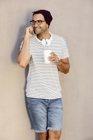 Spectacles guy on phone holding coffee cup, smiling Stock Photo