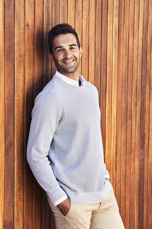 Smiling guy in sweater leaning against wooden wall