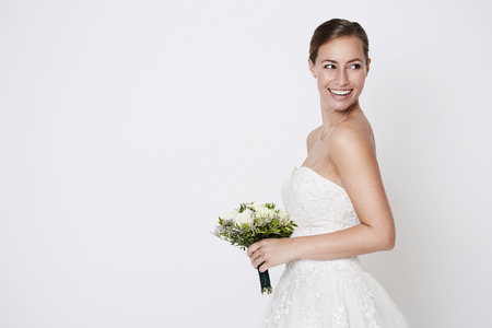 Happy bride about to throw bouquet, studio