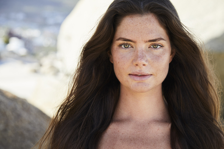 Stunning young brunette beauty on beach, portrait