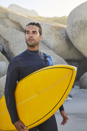 Surfer guy holding board and looking away on beach