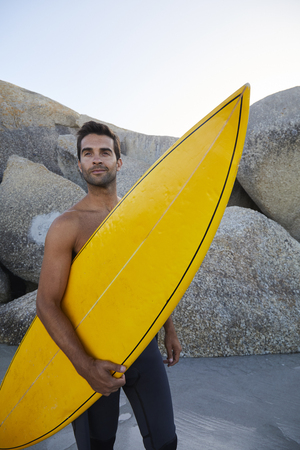 Handsome surf dude holding yellow board on beach Stock Photo