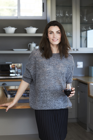 Beautiful brunette with wine in kitchen, portrait Stock Photo
