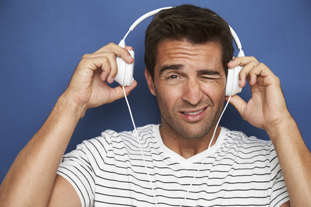 Guy wincing with headphones, portrait Stock Photo