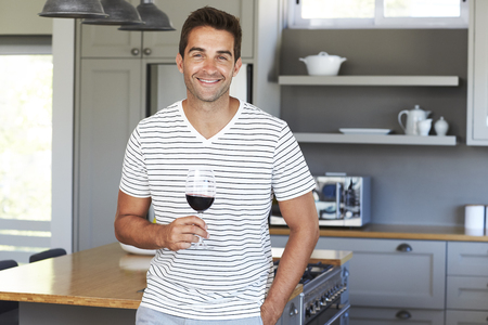 Smiling guy in striped t-shirt holding wine in kitchen