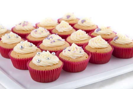 Delicious homemade decorated cupcakes, with vanilla topping, on a white plate