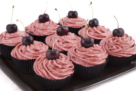 Chocolate flavored cupcakes, with red frosting and a cherry on top, on a black plate on white background