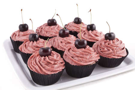 Chocolate flavored cupcakes, with red frosting and a cherry on top, on a white plate on white background