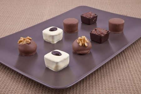 Chocolate bonbon pralines, on a brown plate