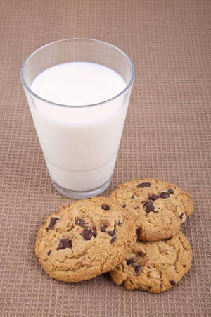 Chocolate chip cookies and a glass of milk, on a brown cotton tablecloth Stock Photo