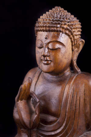 Wooden Buddha statue on black background, with eyes closed