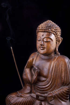 Wooden Buddha statue on black background, with eyes closed, and a burning incense stick Stock Photo
