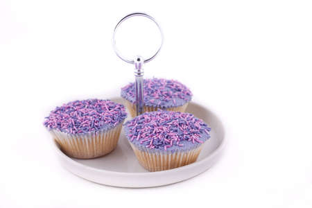 Vanilla cupcakes, decorated with lavender-coloured buttercream and pink & purple sprinkles Stock Photo