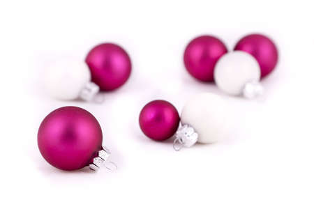 Pink and white christmas balls or decorations, on  a white background, with shallow depth of field