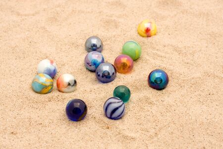 glasses in the sand: colorful marbles in sand