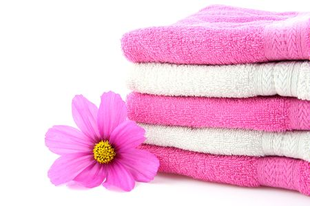 Pink and white towels with one pink flower on white background Stock Photo