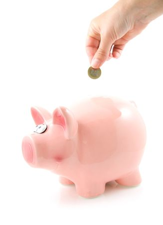 Hand is putting money into piggy bank, isolated on white background photo