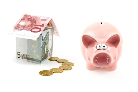 piggy bank and house of banknotes isolated on white background photo