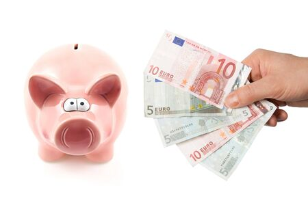 Piggy bank and hand with banknotes isolated on white background photo