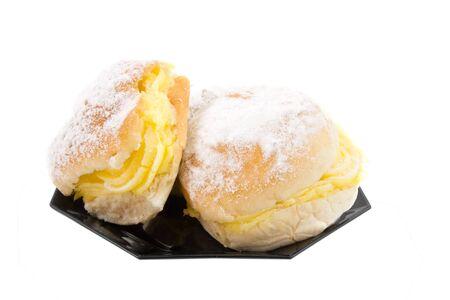 sandwiche: due deliziosi panini crema sulla piastra nera, isolato su sfondo bianco