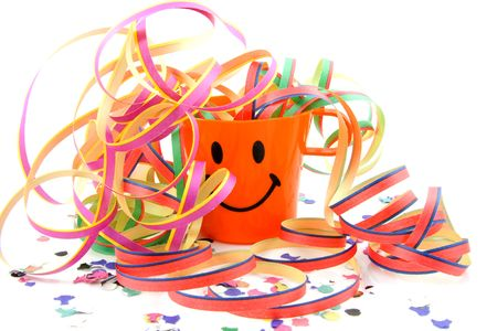 Party cup with streamers and confetti over white background photo