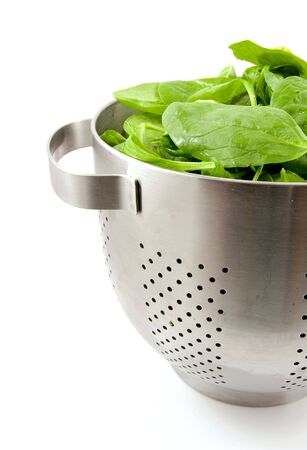 colander filled with fresh spinach over white background photo