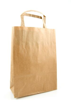 Empty brown paper shopping bag over white background photo