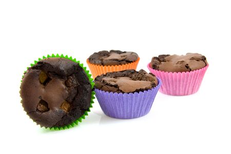Home baked brownie cupcakes in colorful cups over white background photo