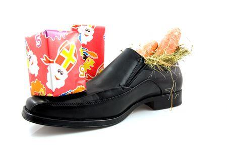 Grote zwarte mannen schoen met wortelen en geschenken voor typische Nederlandse Sinterklaas, op witte achtergrond