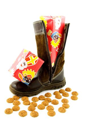 Boot with present and ginger nuts for typical Dutch event: Sinterklaas. Over white background photo