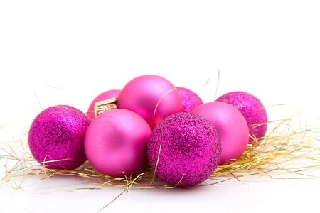 lots of pink christmas balls on golden streamers over white background photo