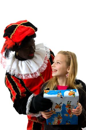 Zwarte piet ( black pete) typical Dutch character part of a traditional event celebrating the birthday of  Sinterklaas in december with young blonde girl over white background Stock Photo - 6038000