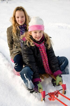 Two girls on a sled in the snow photo