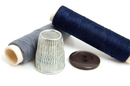 darn: sewing gear with tread, button and thimble over white background Stock Photo
