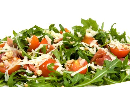 pine kernels: Fresh rucola lettuce with tomatoes, pine kernels and Parmesan cheese over white background