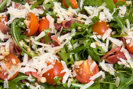 pine kernels: Fresh rucola lettuce with tomatoes, ham, pine kernels and Parmesan cheese in closeup